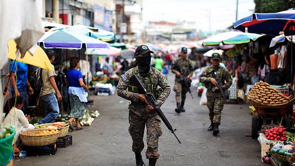 Image: Salvadoran soldiers patrol in downtown San Salvador after six market
