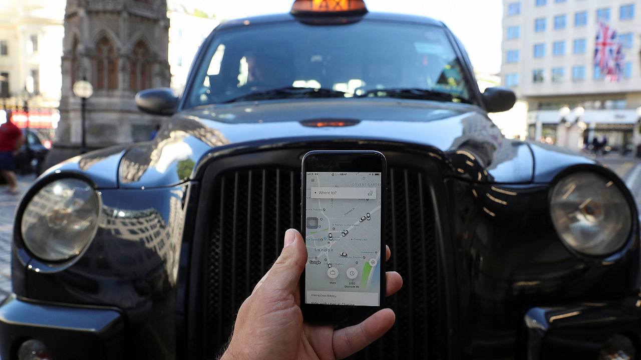 Image: A photo illustration shows the Uber app and a black cab in London,