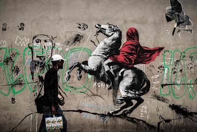 Banksy\'s Napoleon Bonaparte wearing a headscarf, inspired by an original painting by Jacques-Louis David, pictured in northern Paris.