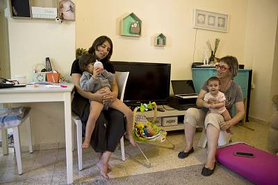 Lilach Naftalyahu, left, holding daughter Ziv while her mother Adele Raemer sits with Raz in Nirim, southern Israel.