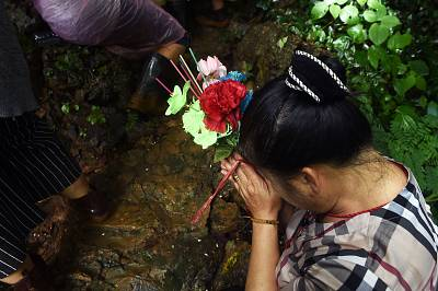 A woman prays near the Tham Luang cave.