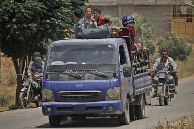 Syrians displaced by government forces\' bombardment in the southern Daraa province ride in a truck near the town of Shayyah.