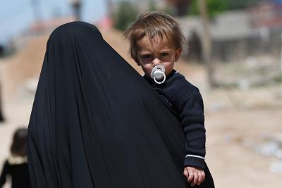 A woman carries a child in a street in Mosul, Iraq, as troops battled to retake the area from ISIS fighters in April 2017.