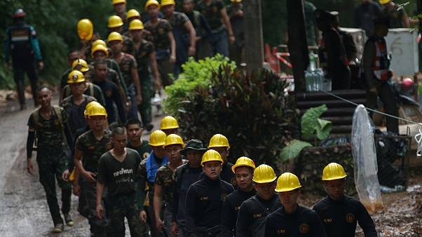 Image: Military personnel walk in line as they prepare to enter the Tham Lu