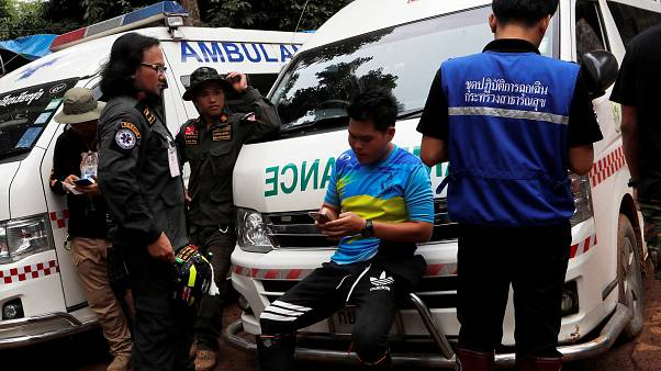 Image: Men standby near ambulances outside Tham Luang cave complex in the n