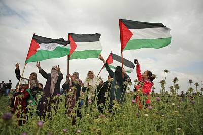 Women wave Palestinian flags and flash the victory gesture during a protest near the fence with Israel in the Gaza Strip on March 30.