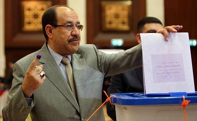 Iraqi Prime Minister Nouri al-Maliki shows his ink-stained finger as he casts his vote at a polling station in Baghdad\'s Green Zone on Wednesday. Iraqis are voting in the first parliamentary election since U.S. troops withdrew.