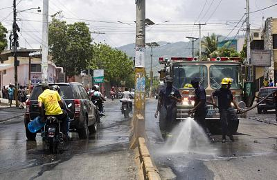 Firefighters clean a street with water after police cleared roadblocks set up by anti-government protesters during a general strike in Port-au-Prince, Haiti, on July 9, 2018.