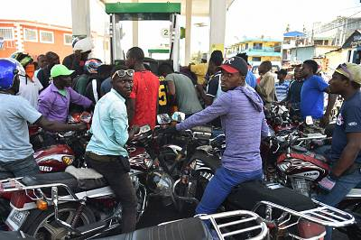 Haitian people wait to purchase fuel at a gas station in the commune of Petion Ville in the Haitian capital Port-au-Prince, one of the few gas stations open during the strike to protest the hike in fuel prices, on July 9, 2018.