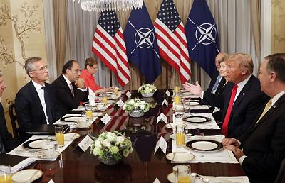 President Donald Trump gestures while speaking to NATO Secretary General Jens Stoltenberg, left, during a breakfast in Brussels on Wednesday.