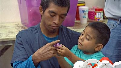 A migrant father recently reunited with his son plays with modeling clay at Annunciation House in El Paso, Texas, on July 11.