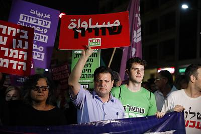"Israeli-Arab Knesset Member Ayman Odeh holds a signs reading ""Equality"" during a protest against the ""nation-state"" law in Tel Aviv before the measure passed."