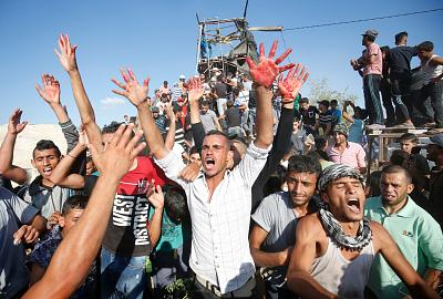 Palestinians react with bloodied hands outside a Hamas outpost that was struck by Israeli bombardment near Khan Yunis in the southern Gaza Strip on July 20, 2018.