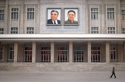A woman walks past portraits of late North Korean leaders Kim Il Sung and Kim Jong Il on the facade of a building in Pyongyang.
