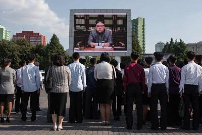 Spectators watch a television news broadcast featuring a statement by North Korean leader Kim Jong Un on a screen outside a train station in Pyongyang.
