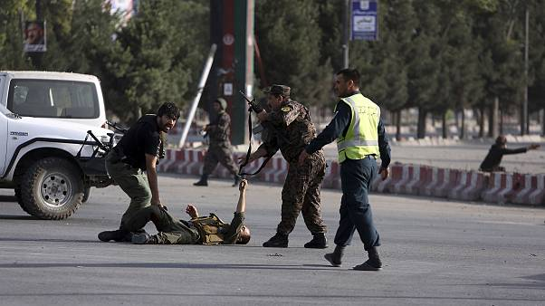 Image: An injured security officer gets help as he lies on the ground after