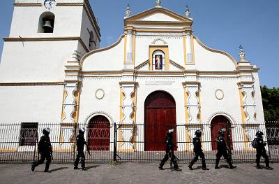 Members of Nicaragua\'s Special Forces walk past a church during clashes with anti-government protesters in the indigenous community of Monimbo in Masaya, Nicaragua on July 13, 2018.