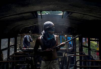 A demonstrator stands inside a bus set alight during a day-long national strike held to mark two months of violent chaos under President Daniel Ortega, in Tipitapa, about 15 miles from Managua on June 14, 2018.
