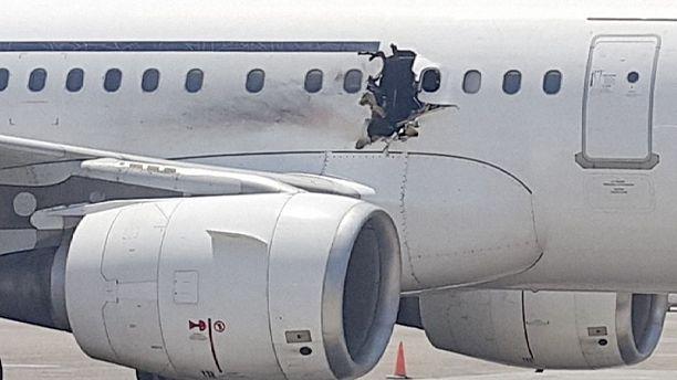Passenger jet lands safely after hole blown in fuselage