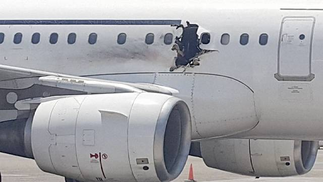 Passenger jet lands safely after hole blown in fuselage