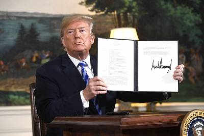 President Donald Trump signs a document reinstating sanctions against Iran at the White House in Washington on May 8.
