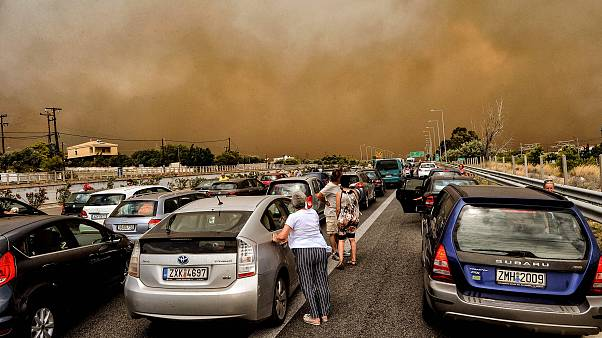 Image: Cars are blocked at the closed National Road during a wildfire in Ki