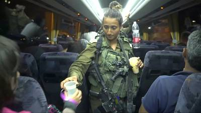 An Israeli solider hands out water on a bus during the evacuation members of the White Helmets on Sunday.