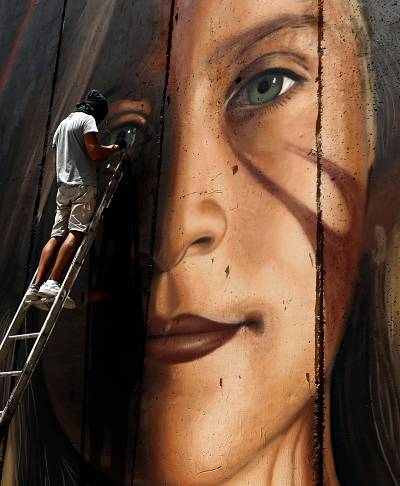 Italian artist Jorit Agoch paints a mural of Ahed Tamimi on Israel\'s separation barrier in the West Bank city of Bethlehem.