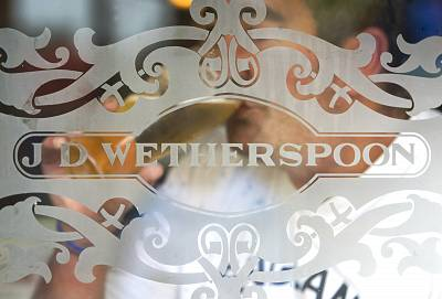 The J.D. Wetherspoon logo is displayed on a glass door at a pub in Hornchurch, England.