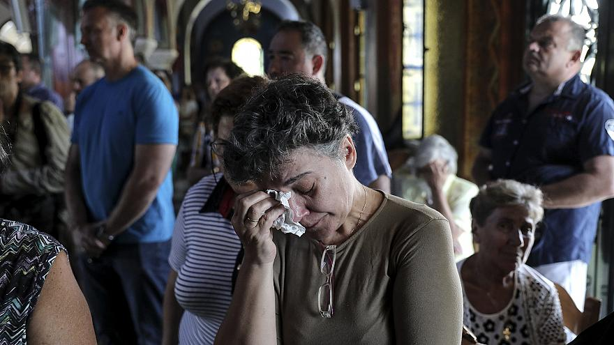 Image: Worshipers attend a memorial service for the victims of a forest fir