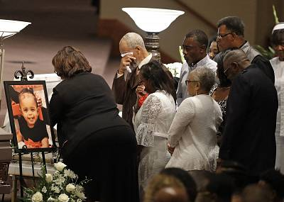 Members of the Coleman family comfort each other at a casket during the showing for five members of the Coleman family on July 28 in Indianapolis.
