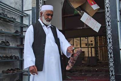 A man holds the shoe of a victim of the attack outside the mosque.