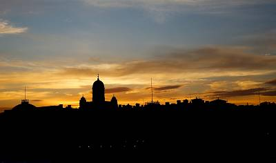 The sun sets behind the presidential palace and cathedral in Helsinki.