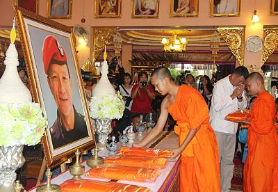 Members of theWild Boar soccer team put saffron robes in front of a portrait of former Thai Navy Seal Petty Officer 1st class Saman Kunan, who died in the Tham Luang cave rescue operations.