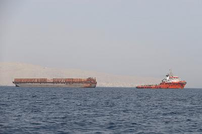 A tugboat moves cargo towards the Strait of Hormuz.
