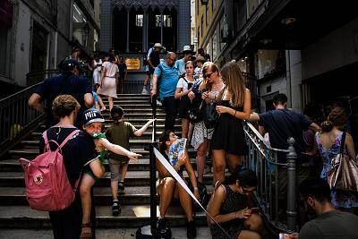 Tourists use fans as the line up near the Santa Justa Elevator in downtown Lisbon on Friday.