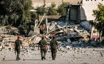 Members of Hamas\' military police walk through a site that was hit by Israeli air strikes in Gaza City on Aug. 9, 2018.