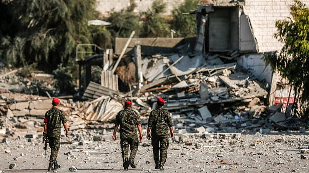 Image: Members of Hamas' military police walk through a site that was hit b