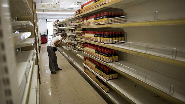 Image: A woman looks at products surrounded by empty shelves at a supermark