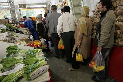 Iranians line up to pay at a grocery store in Tehran.