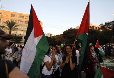 Arab Israelis carry Palestinian flags during a demonstration to protest against the Jewish \'Nation-State\' law in the Israeli coastal city of Tel Aviv on Saturday.