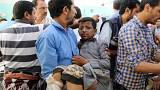 Image: A Yemeni man holds a boy who was injured by an airstrike in Saada
