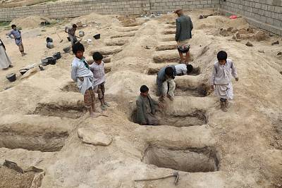 Boys inspect graves prepared for victims of the air strike on Friday.