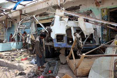 A Yemeni child stands next to a destroyed bus at the site of an air strike in the province of Saada on Friday.