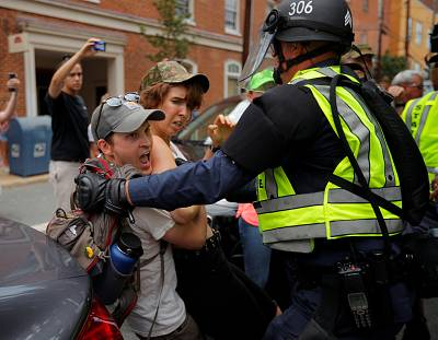"""Police detain a protester at the site where Heather Heyer was killed, on the one year anniversary of the 2017 Charlottesville """"Unite the Right"""" protests, in Charlottesville, Virginia, on Aug. 12, 2018."""