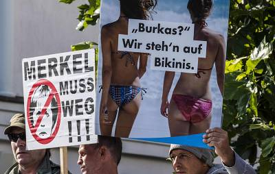 "AfD placards reading ""Merkel must leave!"" and ""Burqas? We prefer bikinis."""