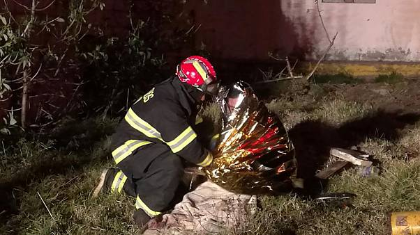 Image: A firefighter assists a victim following a bus crash along a road be