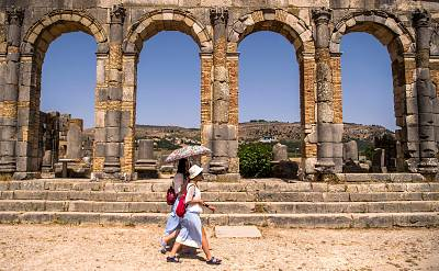 Tourists walk through the ruins of the ancient Roman site of Volubilis, near the town of Moulay Idriss Zerhounon in Morocco\'s north central Meknes region, on July 25, 2018.