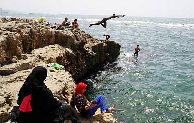 Egyptians jump into the sea to cool off during summer vacation in Alexandria, Egypt, on July 23, 2018.