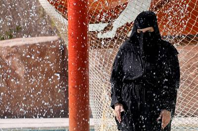 A woman wearing a full veil (niqab) uses a shower to cool off in hot and humid weather inside an Aqua arena during summer holidays at El Ain El Sokhna in Suez, east of Cairo, on July 21, 2018.